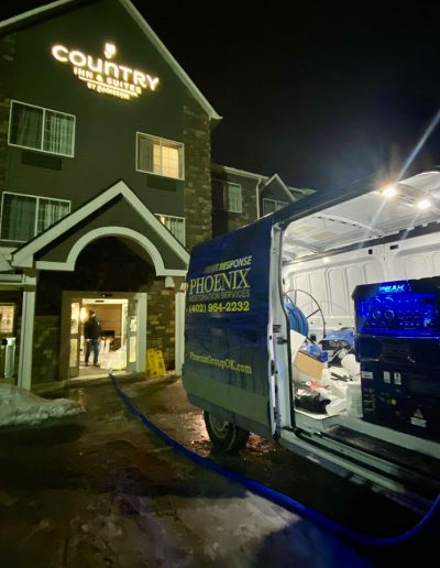 Phoenix Restoration truck and equipment at entrance of Country Inn & Suites