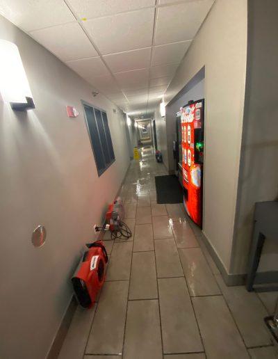 wet tile floor with fans in hallway of Country Inn & Suites